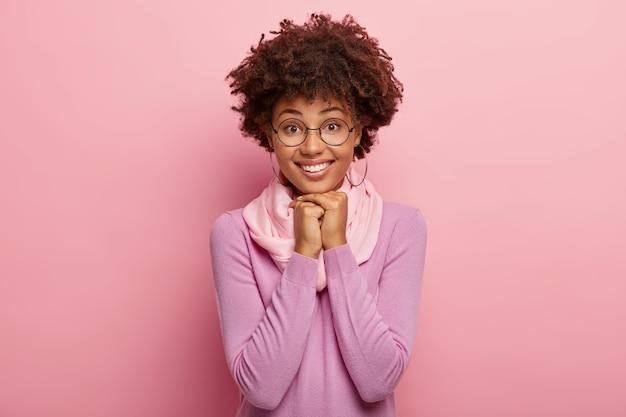 La donna sorridente ottimista indossa un maglione a maniche lunghe, tiene le mani premute insieme sotto il mento