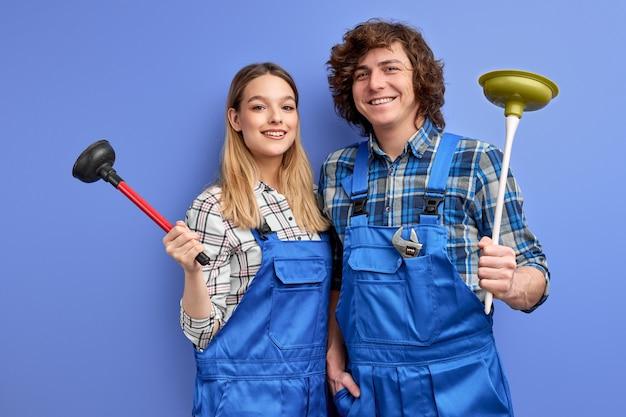 Оптимистичная бригада сантехников, одетых в синюю униформу с плунжером, радуется