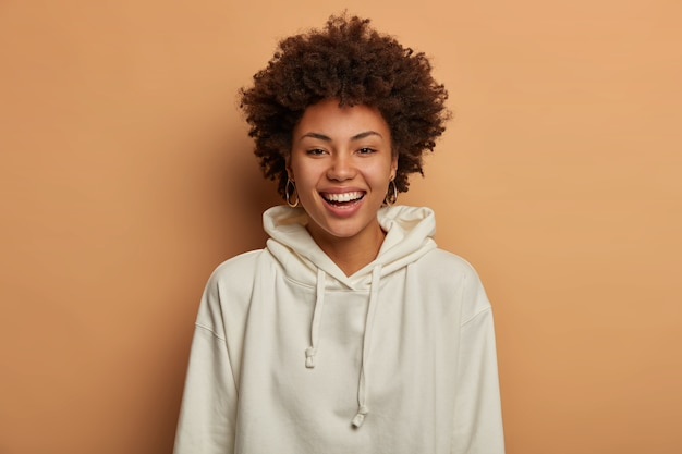 Optimistic teenage girl dressed in casual white sweatshirt, smiles happily, stands against brown space, hears funny joke from friend