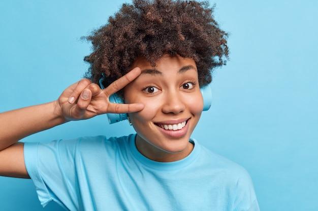 곱슬 덥수룩 한 머리카락을 가진 낙관적 인 십대 소녀는 얼굴 미소를 통해 평화 서명을 행복하게 즐기고 무선 헤드폰에서 우수한 음악 재생 목록을 푸른 벽에 고립 된 자유 시간이 있습니다