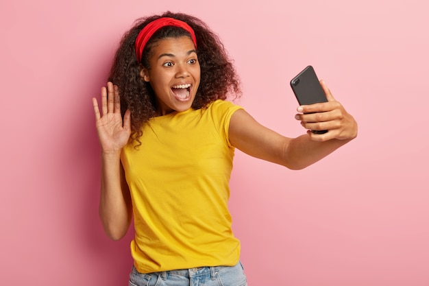 黄色のtシャツでポーズをとる巻き毛の楽観的な10代の少女