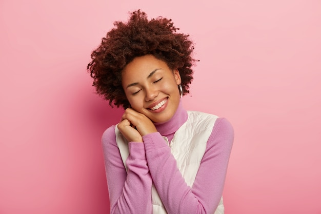 Optimistic teenage girl with natural curly hair, tilts head and smiles joyfully, leans on hands, keeps eyes shut, wears comfortable clothes, stands in cute pose.