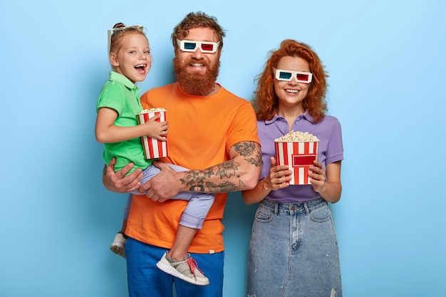 Optimistic three family members laugh happily, watch comedy in cinema together, enjoy eating delicious popcorn