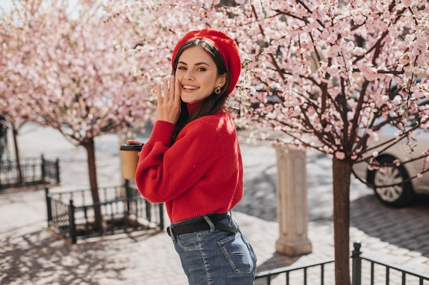 Optimistic woman in bright outfit is smiling cute near sakura. pretty lady in red sweater anf hat posing in good mood in city garden