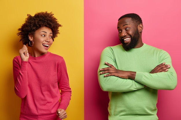 Optimistic woman dances carefree, has fun together with dark skinned boyfriend, looks happily each other, dressed in bright clothes, isolated on pink yellow wall. people, lifestyle concept