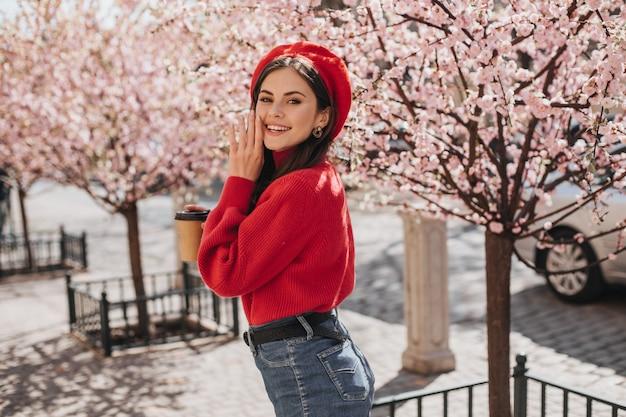 Оптимистичная женщина в ярком наряде мило улыбается возле сакуры. красивая дама в красном свитере и шляпе позирует в хорошем настроении в городском саду