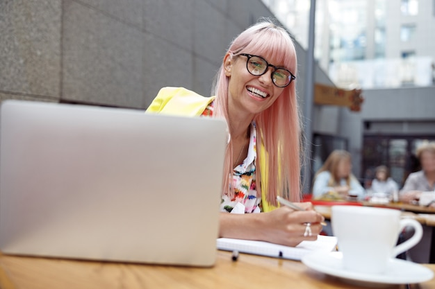 カフェで屋外でメモを取る眼鏡の楽観的な女性