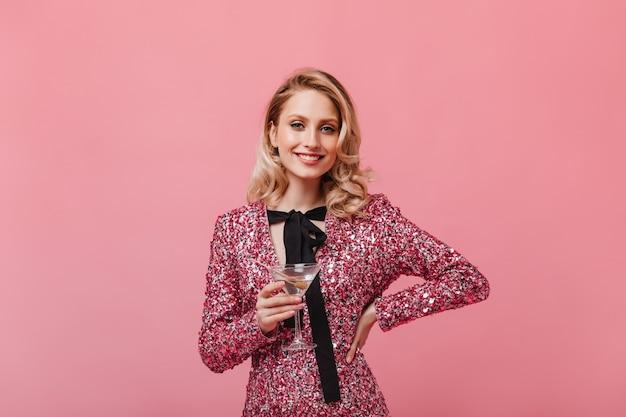 미소로 스마트 드레스에 낙관적 인 여자가 정면을 바라보고 마티니 잔을 보유하고 있습니다.