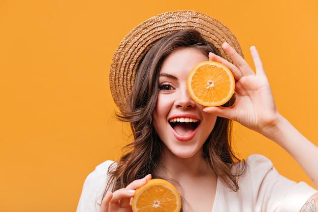 밀짚 모자에 낙관적 인 여자는 카메라를 보면서 오렌지와 미소로 그녀의 눈을 덮습니다.