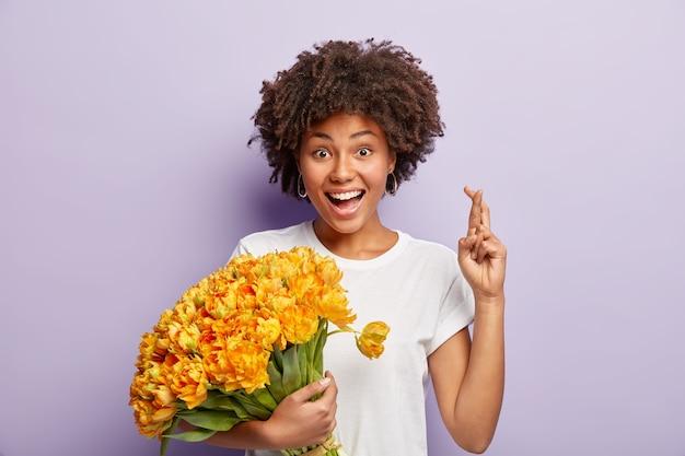 낙관적 인 여자는 진심으로 좋은 건강을 믿고, 교차 손가락으로 손을 들고, 아름다운 노란색 봄 꽃을 들고, 행복한 표정을 짓고, 보라색 벽 위에 고립 된 흰색 티셔츠를 입습니다.