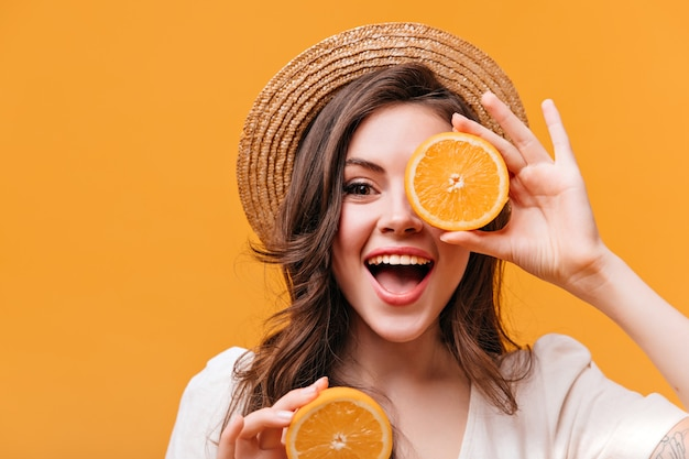 Optimistic woman in straw hat covers her eyes with orange and smiles while looking at camera.