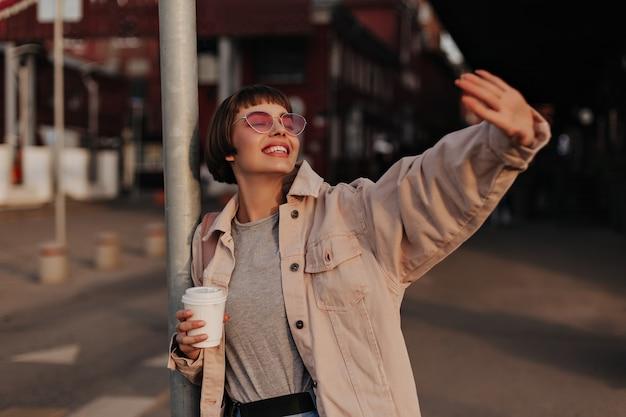 屋外でお茶を保持しているブルネットの髪を持つ楽観的な女性