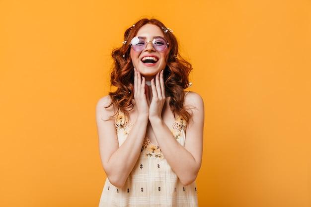 곱슬 머리를 가진 낙관적 인 여자는 진심으로 웃는다. 선글라스와 노란색 탑 카메라를보고있는 여자.