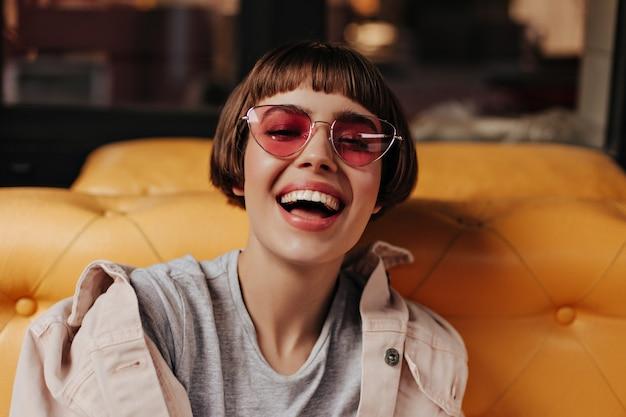 カフェで笑っている短い髪の楽観的な女性