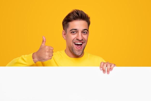楽観的な若いひげを生やした男は幸せそうに笑って、黄色の背景に対して空白の白いポスターの後ろに立っている間、承認の親指を立てるジェスチャーを示しています