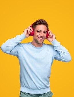 Оптимистичный молодой бородатый мужчина в повседневной одежде и беспроводных наушниках веселится и наслаждается хорошей музыкой на желтом фоне