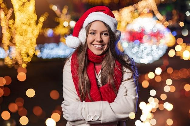 暖かい服とサンタの帽子をかぶった楽観的な若い女性は、夜のぼやけたクリスマスライトに立ちながら笑顔と見ています
