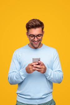 Оптимистичный молодой парень с помощью смартфона