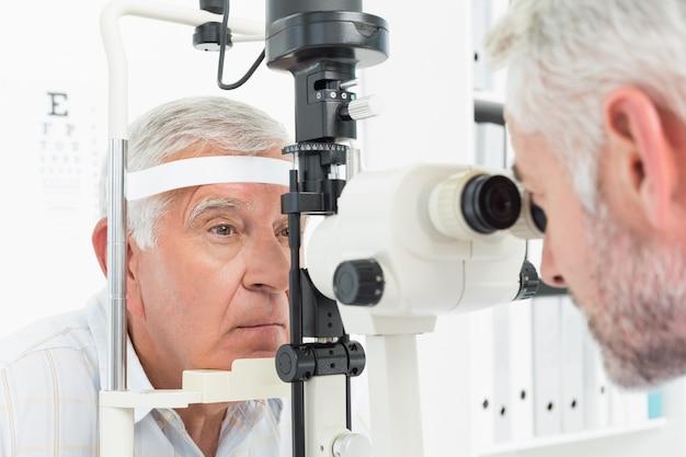 Оптометрист проводит зрение для старшего пациента