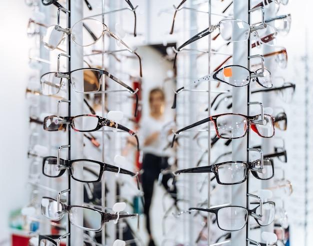 ぼやけた背景に眼鏡を見せている検眼医、眼鏡技師または眼科医。店内にはたくさんの眼鏡があります。
