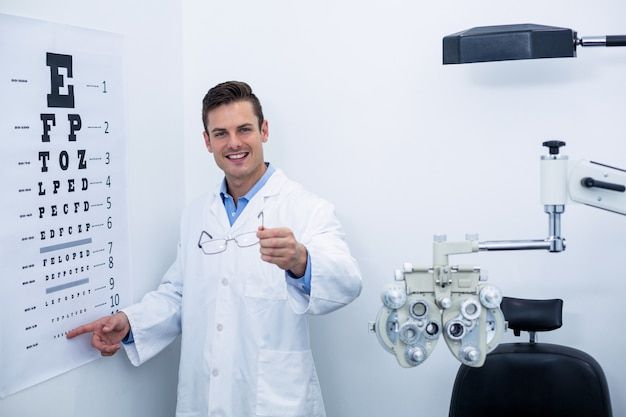 Optometrist pointing at eye chart