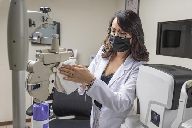 Optometrista con maschera facciale disinfettante attrezzature speciali per la cura degli occhi - il nuovo concetto normale