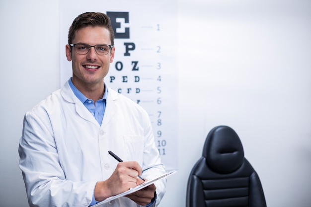 Optometrist writing on clipboard