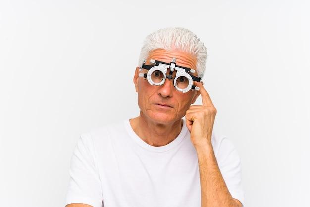 Старший кавказский человек нося рамку optometrist пробную указывая его висок с пальцем, думая, сфокусировал на задаче.