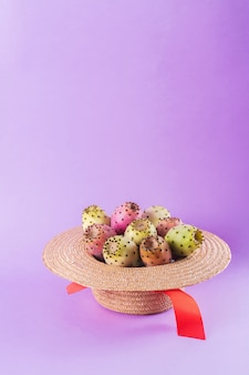 Opuntia fruit in a straw hat on a trendy purple background