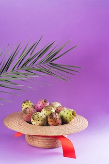 Opuntia fruit in a straw hat with a palm leaf on a trendy purple background