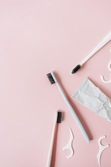 Средства по уходу за полостью рта, зубные щетки, зубная паста, зубная нить на розовом. плоская планировка, вид сверху минимальная концепция гигиены полости рта