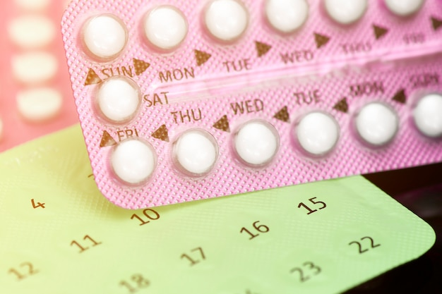Oral contraceptive pill education concept on dark background.