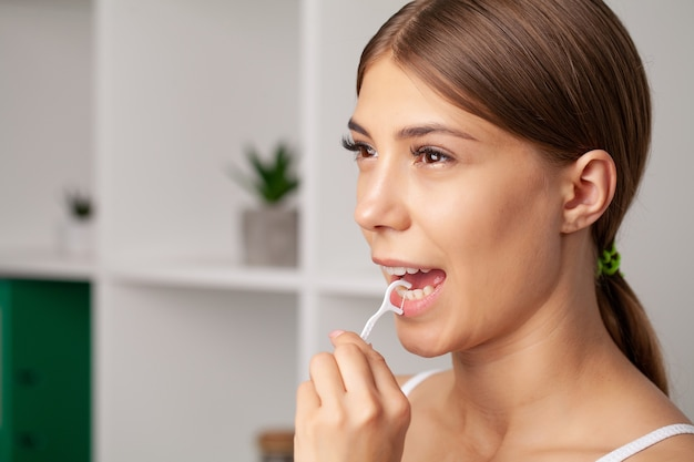 Oral hygiene and health care, smiling women use dental floss white healthy teeth.