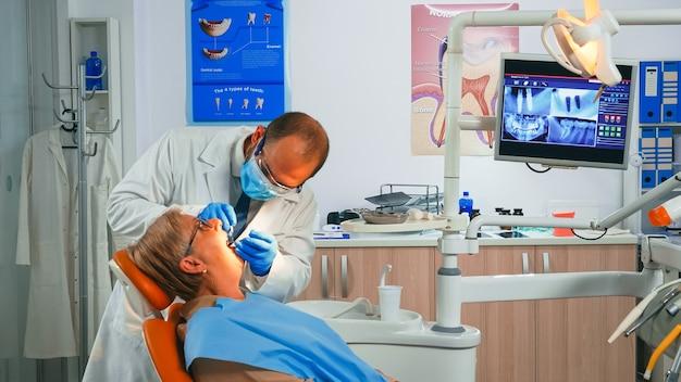 口腔外科医は、年配の女性の口に取り付けられたミラー歯冠でチェックします。看護師がランプを点灯し、医師が口腔病学の椅子に座っている患者に話しかけ、手術の準備をします。