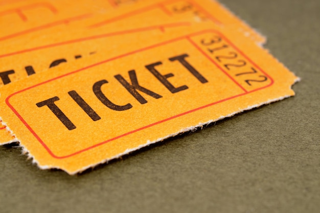 Orange admission tickets on a mottled brown paper background.