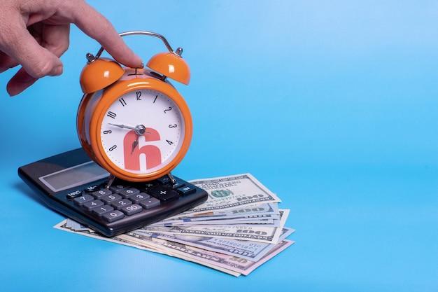 오렌지 알람 시계와 돈 지폐 달러에 계산기. 사업 계획, 금융, 저축, 세금 납부 마감일에 대한 개념.
