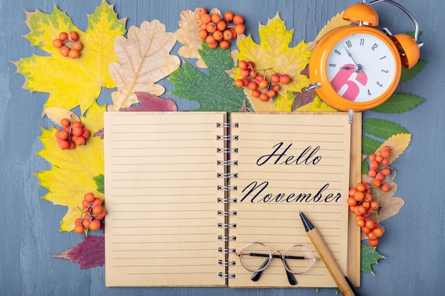 Orange alarm clock, craft notebook with the inscription hello november, pen and glasses on a background of autumn dry colorful leaves. working day planning concept. plans for november concept.