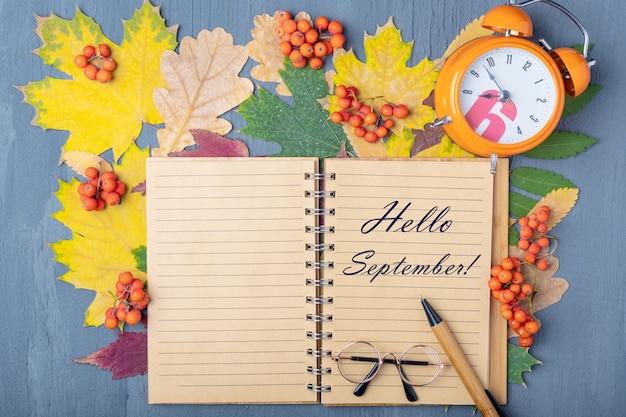 Оранжевый будильник, ремесленная тетрадь с надписью hello september, ручка и очки на фоне осенних сухих разноцветных листьев. концепция планирования рабочего дня. планы на сентябрьский концепт.