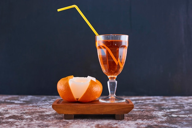 Апельсин и стакан сока с желтой трубкой на деревянном блюде на мраморе посередине. фото высокого качества