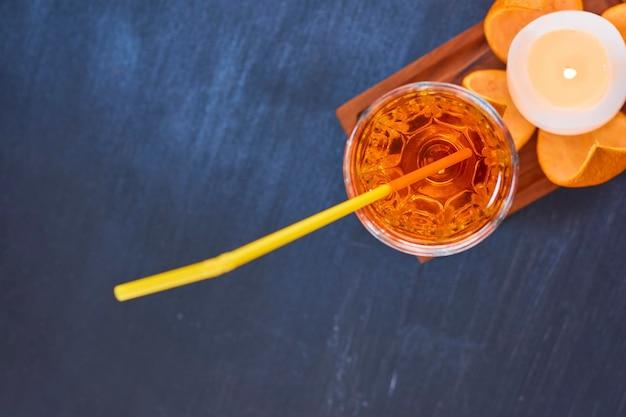 Апельсин и стакан сока с желтой трубкой на деревянном блюде в верхнем углу. фото высокого качества