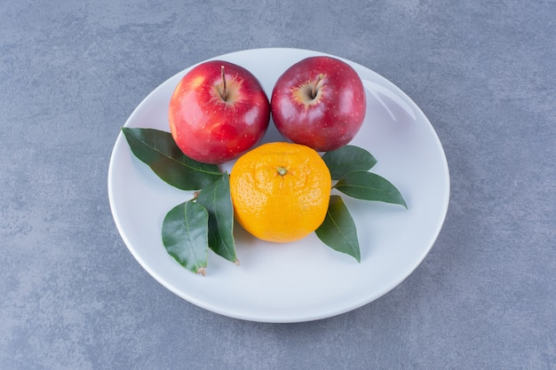 大理石のテーブルの上のプレートに葉を持つオレンジとリンゴ。