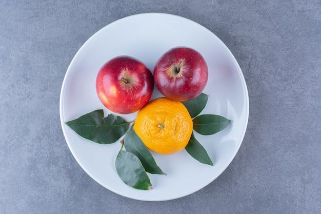 오렌지와 사과 잎이 어두운 표면에 접시에