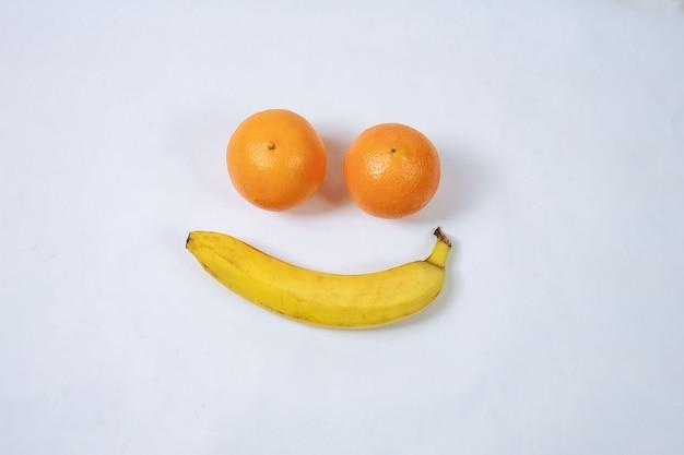 Апельсин и банан, образуя смайлик, изолированные на белом. улыбка. грусть.