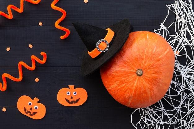오렌지와 블랙 할로윈 플랫레이. 분필 비문 boo, 펠트, 얇은 명주 그물, 검은 배경에 거미줄에서 호박.