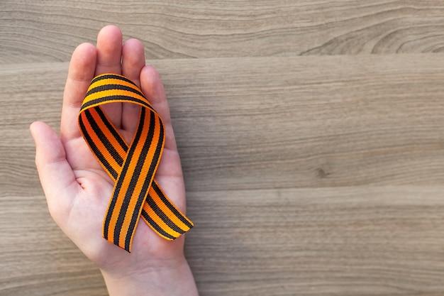 Оранжевый и черный полосатый символ ленты 9 мая в руках, изолированных на белой стене. день победы