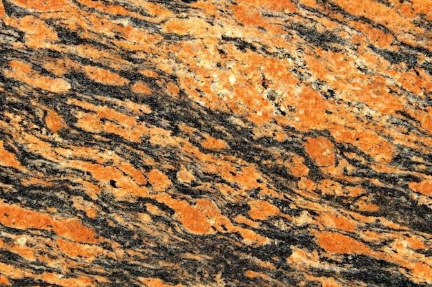 흰색 반점이 있는 주황색과 검정색 화강암 질감. 자연석 배경