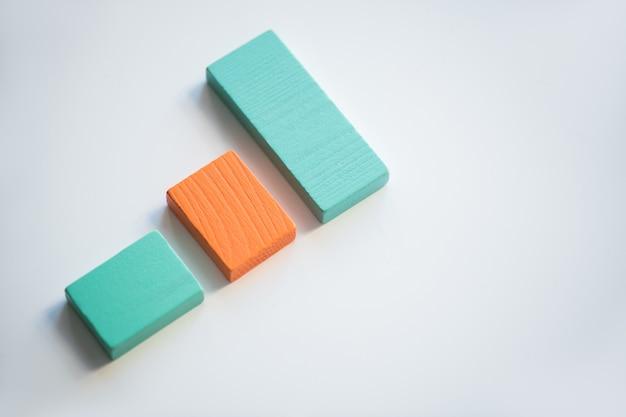 それらを囲むコピースペースと白い背景に対してチャートを構成するオレンジと青の平らな木製のレンガ