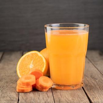 Апельсиновый и морковный сок в стакане с фруктами над деревянным столом.