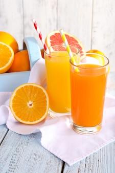 냅킨에 안경에 오렌지와 당근 주스와 나무 벽 배경에 나무 테이블에 나무 상자에 신선한 과일