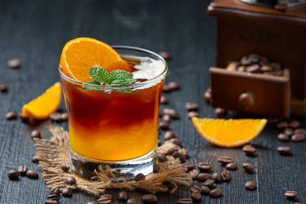 暗い表面にオレンジとコーヒーのカクテル。